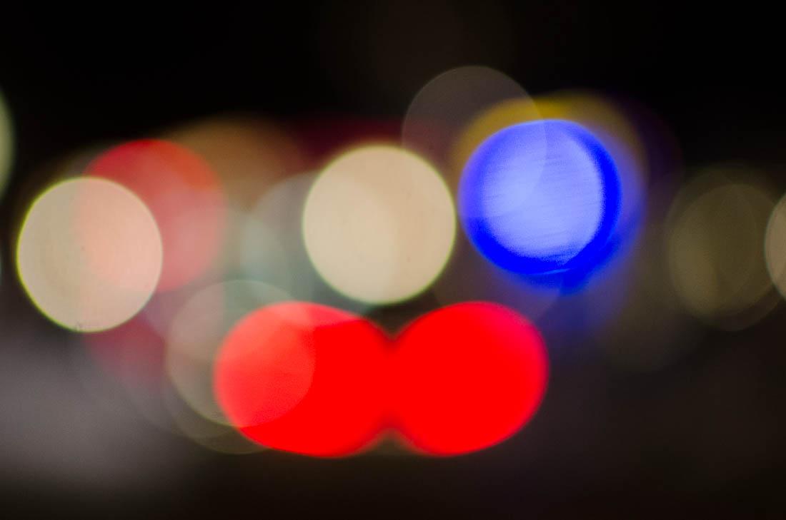 Světlomety aut a pouliční lampy v noci.