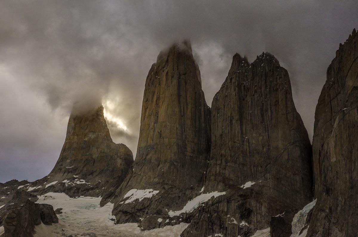 Detail tří věží, částečně zahalených mracích těsně před soumrakem.