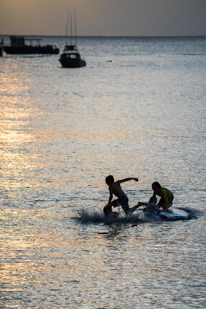 Hrající si děti a jejich siluety v zapadajícím slunci na pláži Hanalei